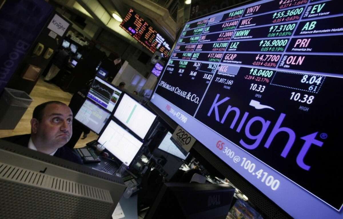 Specialist Peter Giacchi looks at the price of Knight at his post on the floor of the New York Stock Exchange Wednesday. Traders' attention was diverted to unusually sharp moves in a number of stocks shortly after the opening bell. The New York Stock Exchange says it is reviewing trades in 140 stocks.