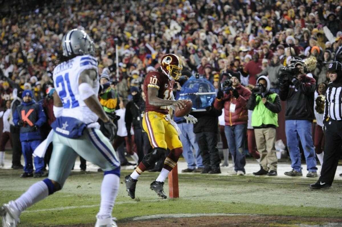 Washington Redskins quarterback Robert Griffin III scores a third-quarter touchdown while Mike Jenkins (21) follows the play. The Redskins won 28-18.