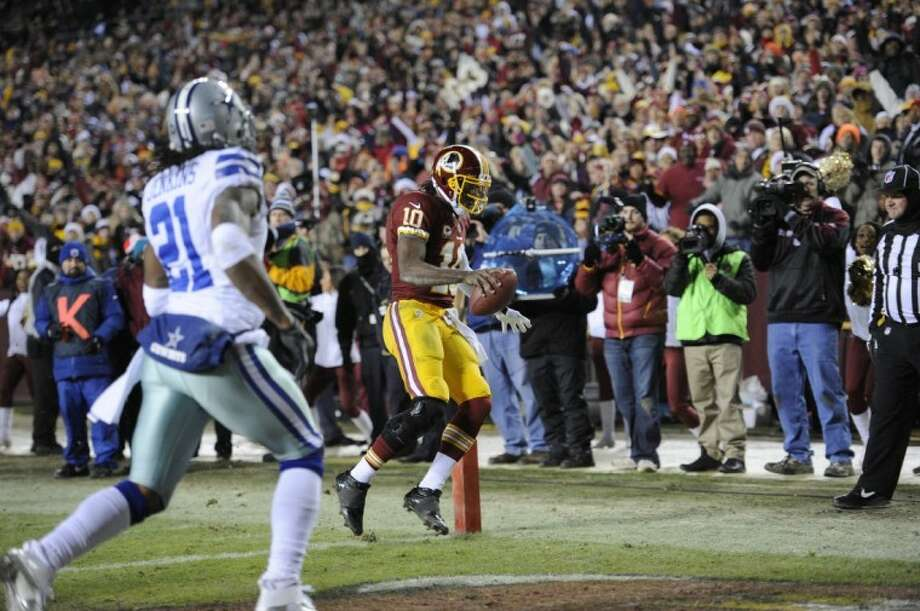 Washington Redskins quarterback Robert Griffin III scores a third-quarter touchdown while Mike Jenkins (21) follows the play. The Redskins won 28-18. Photo: Nick Wass