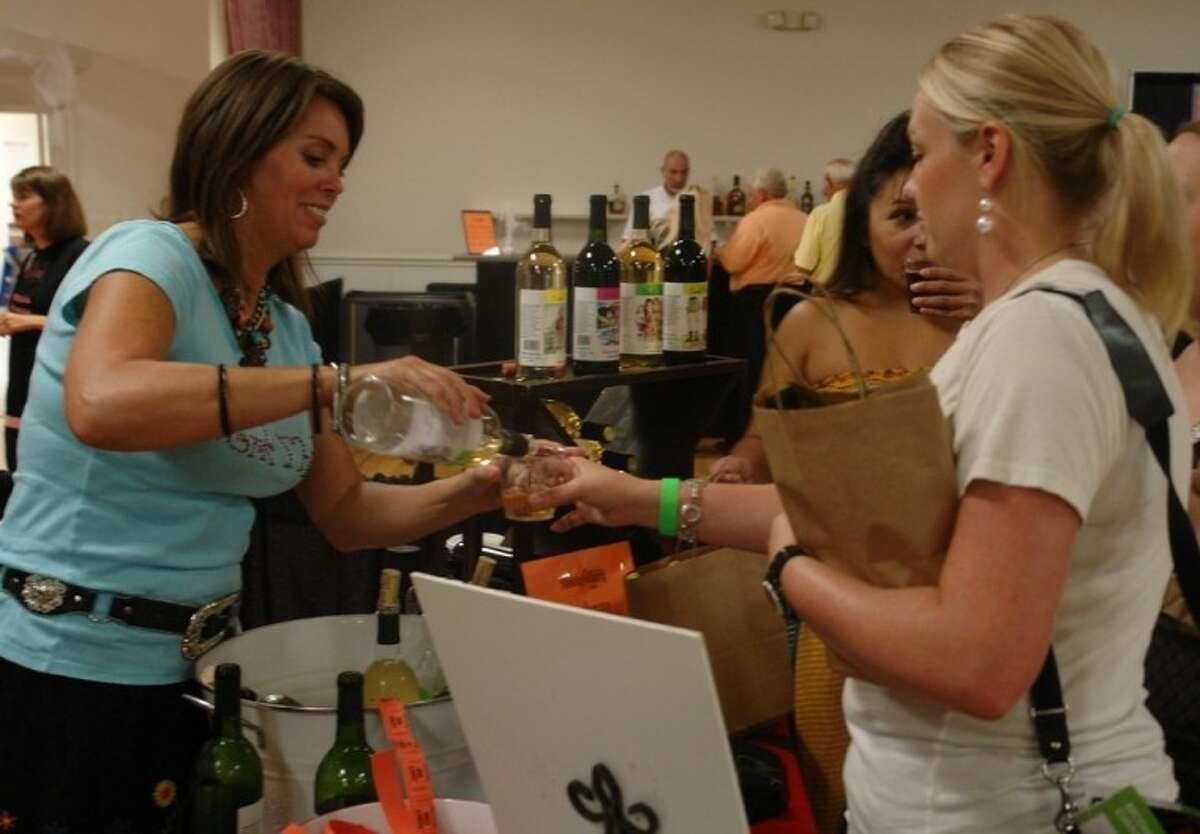 Attendees get a sample of wine from Karla Nash, owner of Cork This!, a speciality boutique winery in Montgomery, Thursday evening at the Experience Montgomery Showcase inside the Lake Conroe Event Center. The winery is this year's recipient of the Business of the Year award from the Historic Montgomery Business Association.