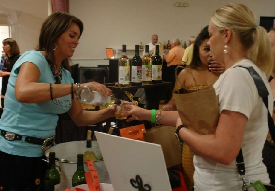 Attendees get a sample of wine from Karla Nash, owner of Cork This!, a speciality boutique winery in Montgomery, Thursday evening at the Experience Montgomery Showcase inside the Lake Conroe Event Center. The winery is this year's recipient of the Business of the Year award from the Historic Montgomery Business Association. Photo: Jonathan Garris