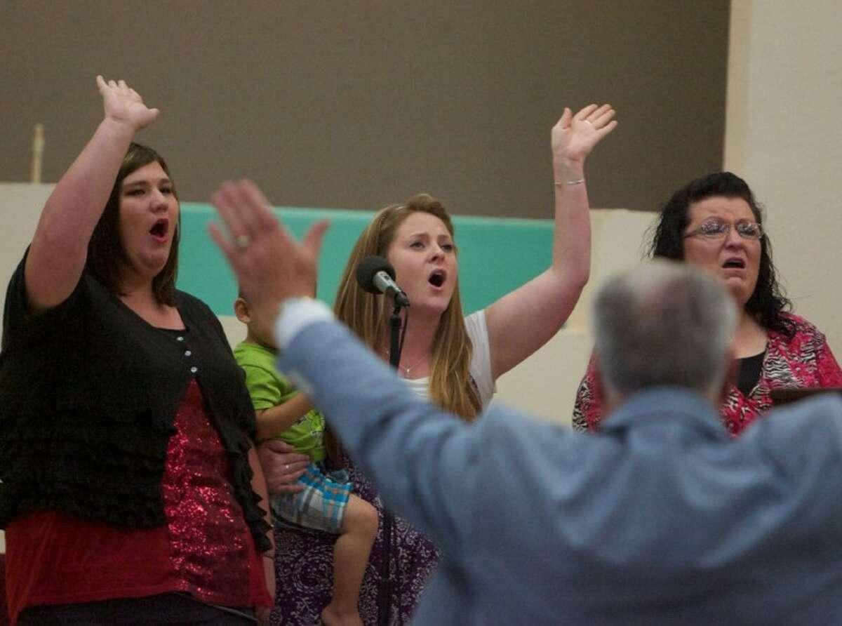 Members of the Bible Baptist Church congregation take part in a worship service Saturday during the celebration of the church's new building at 10984 FM 1485 and Waukeegan.