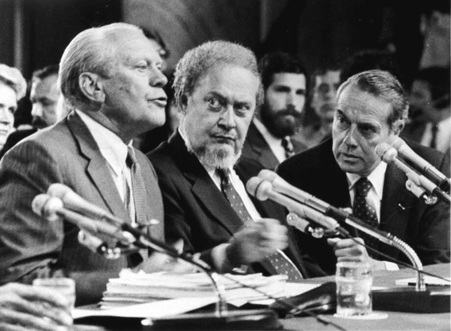 "FILE - In this Sept. 15, 1987 file photo, former President Gerald Ford, left, introduces Supreme Court Associate Justice nominee Robert Bork, as the Senate Judiciary Committee began confirmation hearings on the nomination on Capitol Hill. Ford praised Bork as being ""uniquely qualified"" for the post. At right is Sen. Robert Dole, R-KS, who also made a statement on Bork. Robert Bork, whose failed Supreme Court nomination made history, has died. Photo: CHARLES TASNADI"
