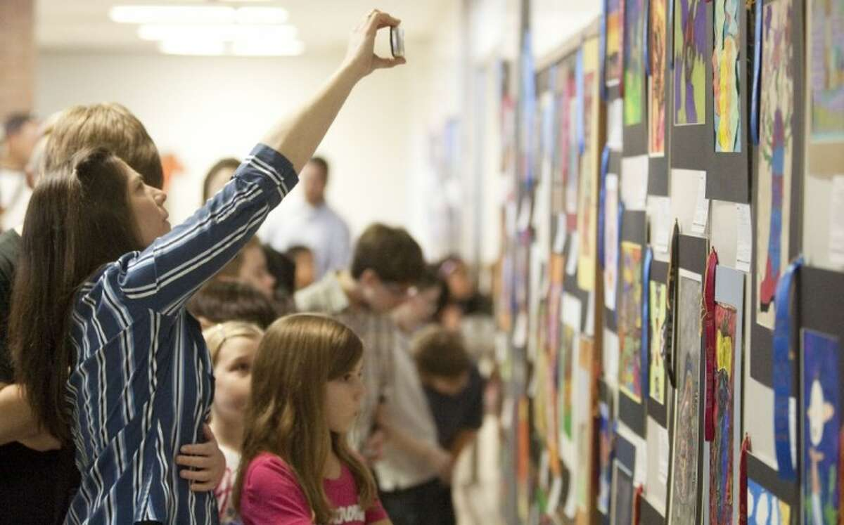 People take pictures of artwork at the Conroe ISD Western Art Show in conjunction with the Houston Livestock Show and Rodeo Saturday at Conroe High School.
