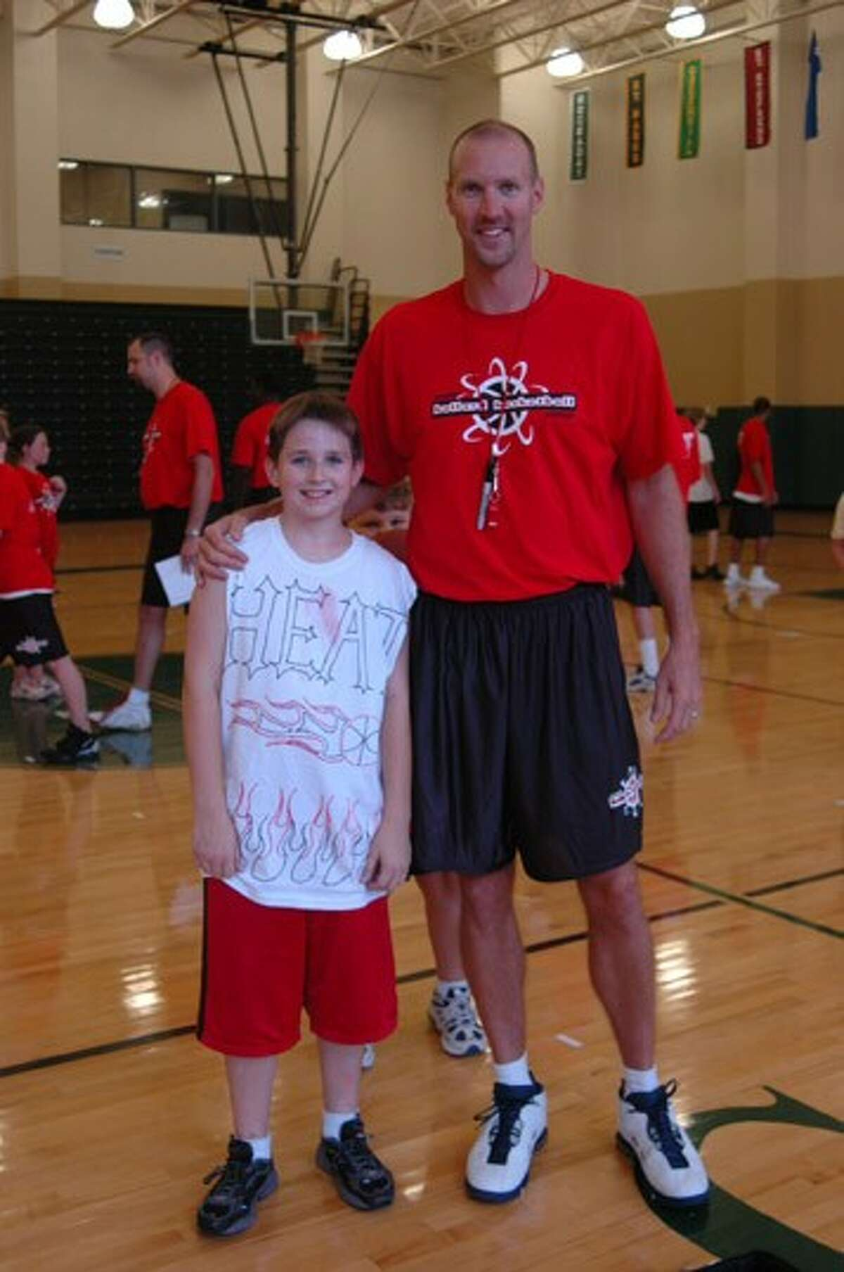 Former Houston Rockets player Matt Bullard poses with one of his summer basketball camp students. Bullard will host his 19th annual camp Monday through Friday at The John Cooper School in The Woodlands.