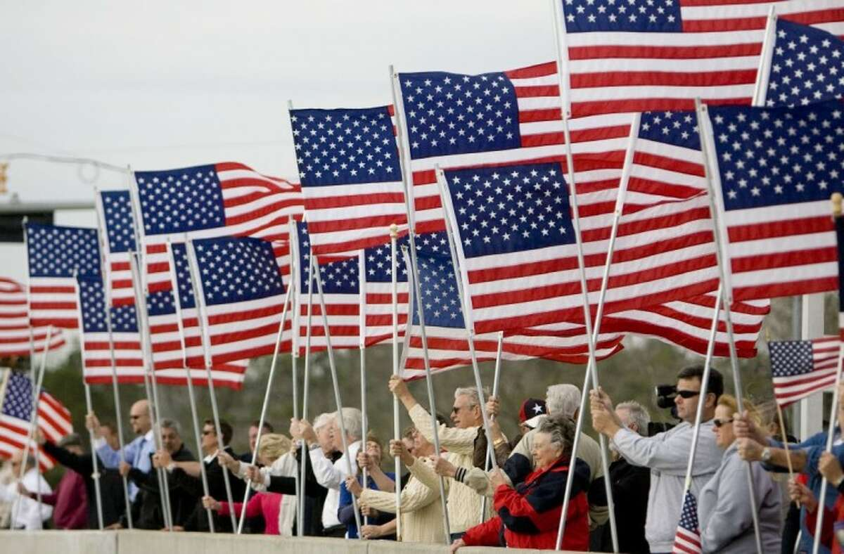 Citizens line the Wilson Road overpass in Conroe with American flags Monday in honor of fallen Marine Cpl. Joseph Logan.