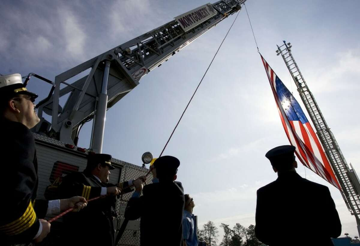 Firefighters with the North Montgomery County Fire Department and Willis Fire Department hoist a large American flag above the FM 1097 bridge Monday in honor of fallen Marine Cpl. Joseph Logan.