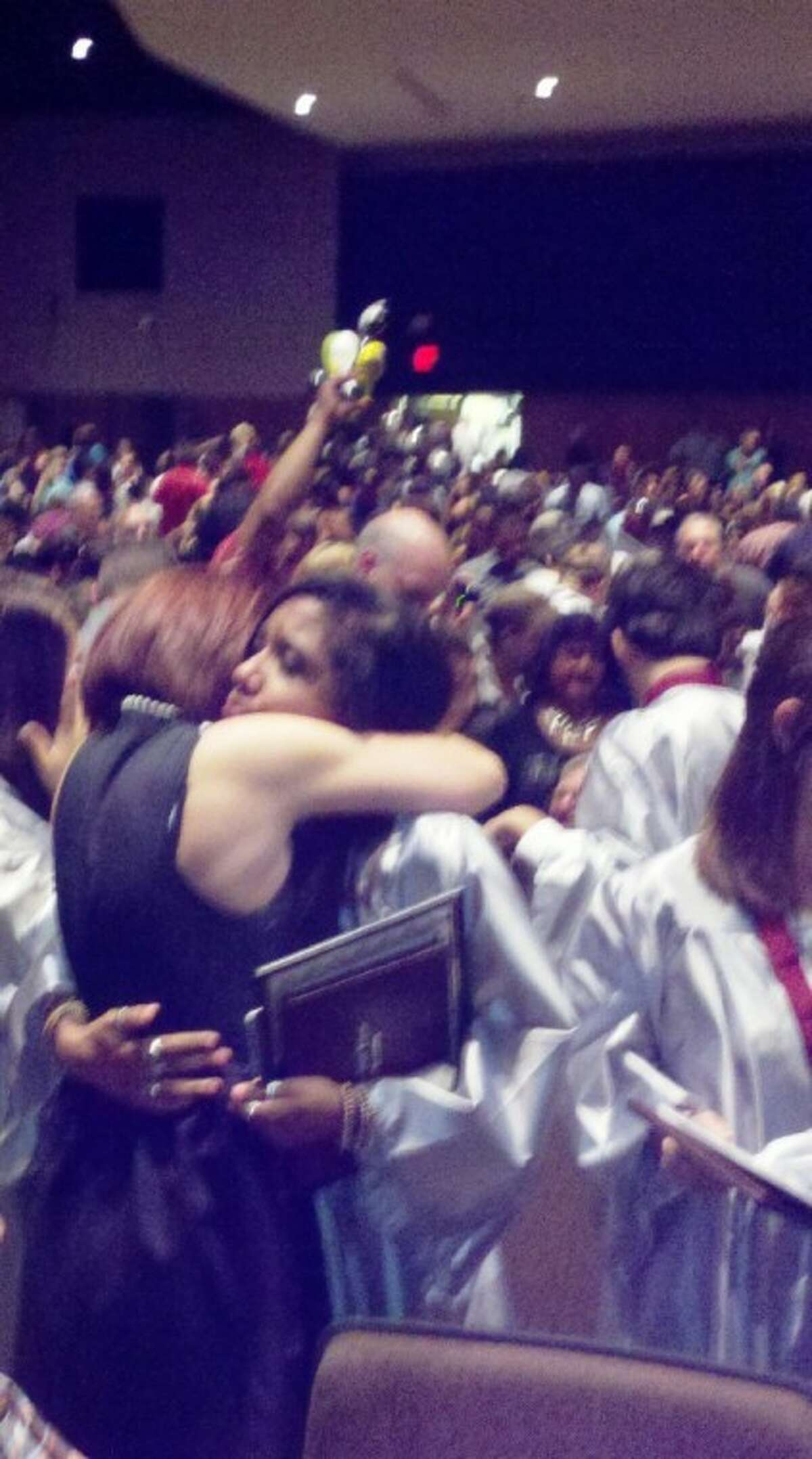A Hauke Alternative High School graduate emotionally embraces a family member after receiving her diploma at Hauke's commencement ceremony at Conroe High School Thursday evening.