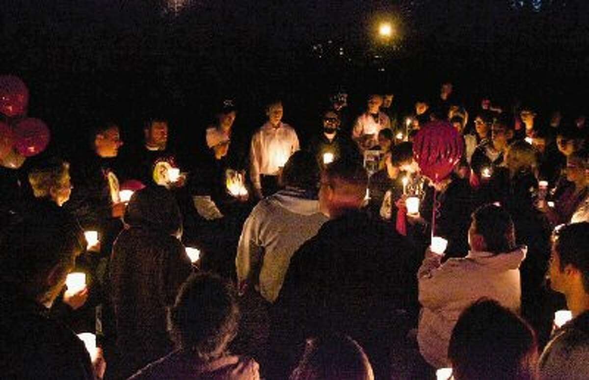 Nearly 100 friends and family members of Toni Lynn, Taylor, 19, take part in a candlelight vigil Tuesday night off of FM 1484 and Cedar Lane Road.
