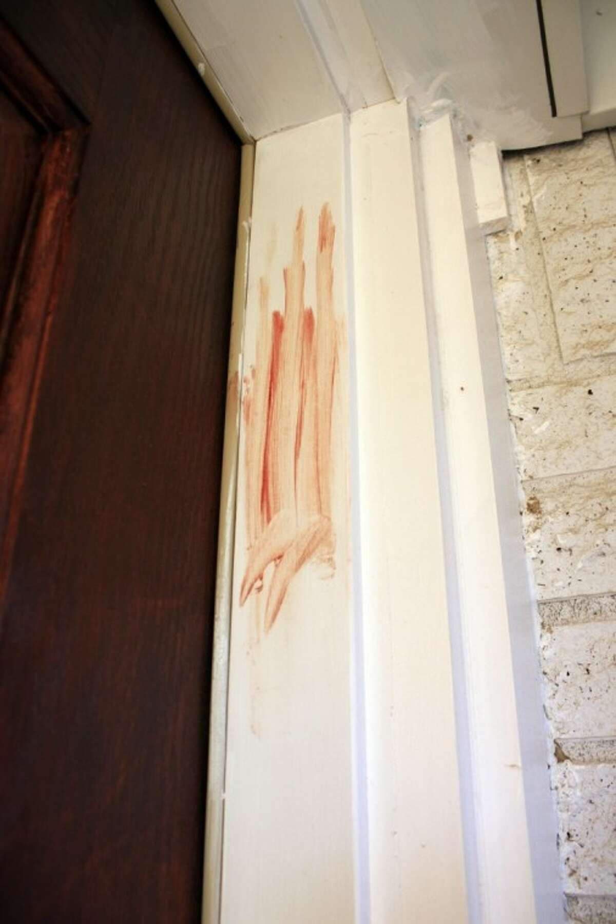 Blood is smeared on the door frame at a home in Richland Hills, Texas, where Brent Troy Bartel is accused of using a box cutter to carve a pentagram in his six-year-old son's back on Wednesday. Bartel was charged with aggravated assault with a deadly weapon and was jailed in lieu of $500,000 bond.
