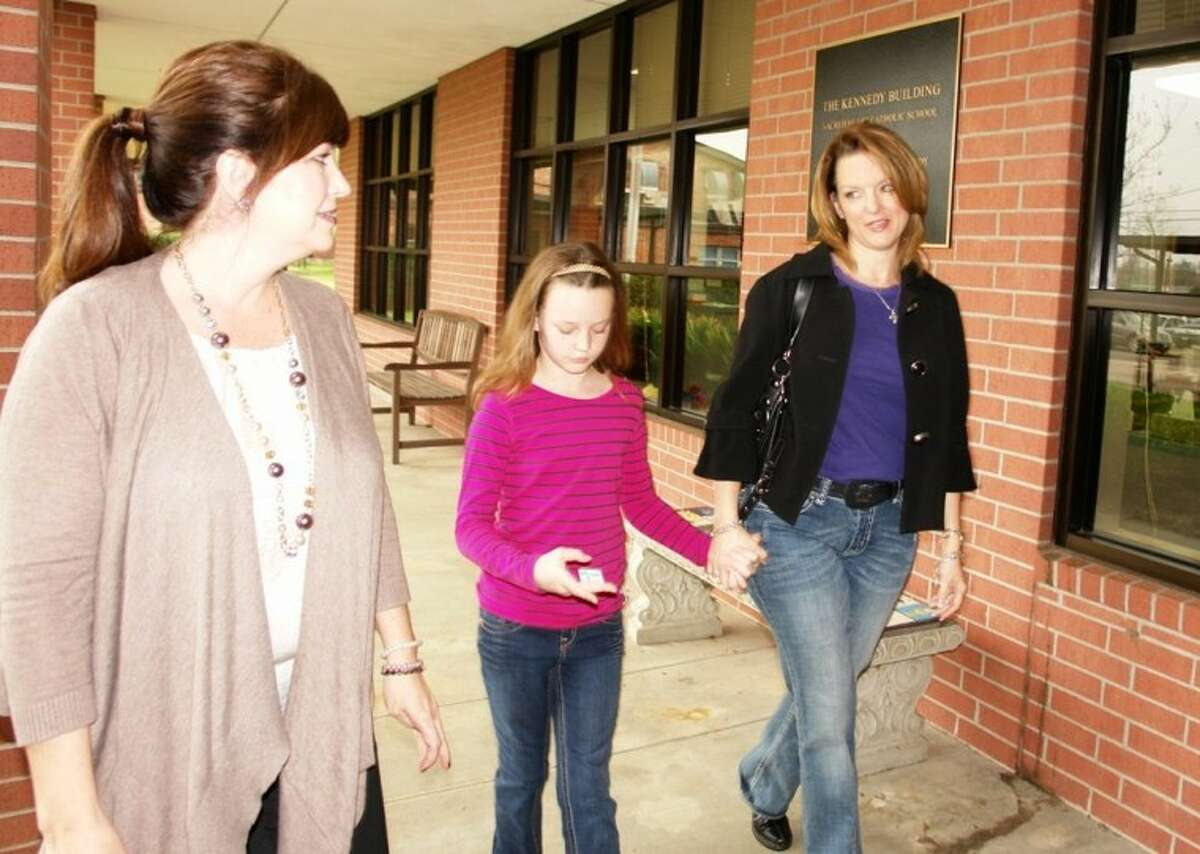 Stephanie Hill, Sacred Heart Catholic School board member, gives a campus tour to Marjorie Moreland and her third-grade daughter, Natalie, Thursday during an open house on campus as part of Catholic Schools Week.