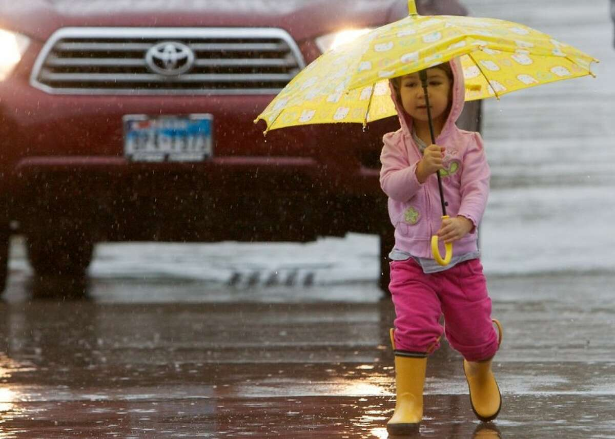 Lauren Davie, 2, of The Woodlands, holds an umbrella as she makes her way through the parking lot at the Panther Creek Shopping Center in The Woodlands. Heavy rains fell throughout the county Thursday.