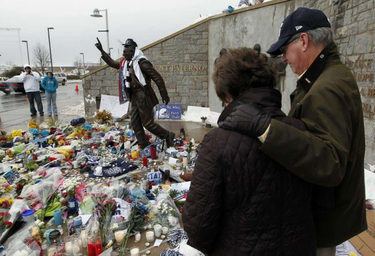 Margaret Bigham, left, and Jake Bigham, from near Charleston, S.C., pause ion remembrance around a statue of Penn State football coach Joe Paterno, outside Beaver Stadium on the Penn State campus Monday in State College, Pa.