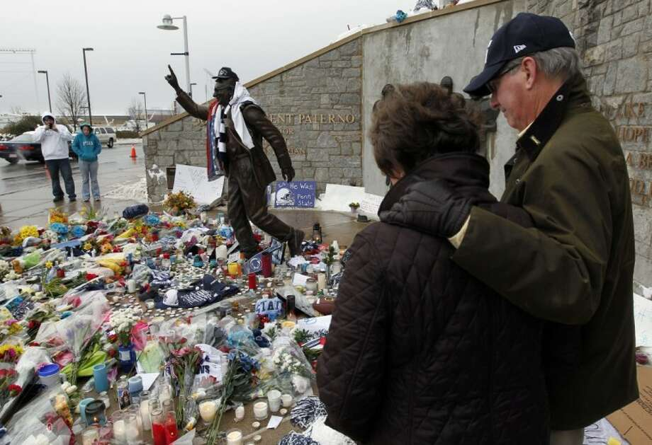 Margaret Bigham, left, and Jake Bigham, from near Charleston, S.C., pause ion remembrance around a statue of Penn State football coach Joe Paterno, outside Beaver Stadium on the Penn State campus Monday in State College, Pa. Photo: Alex Brandon