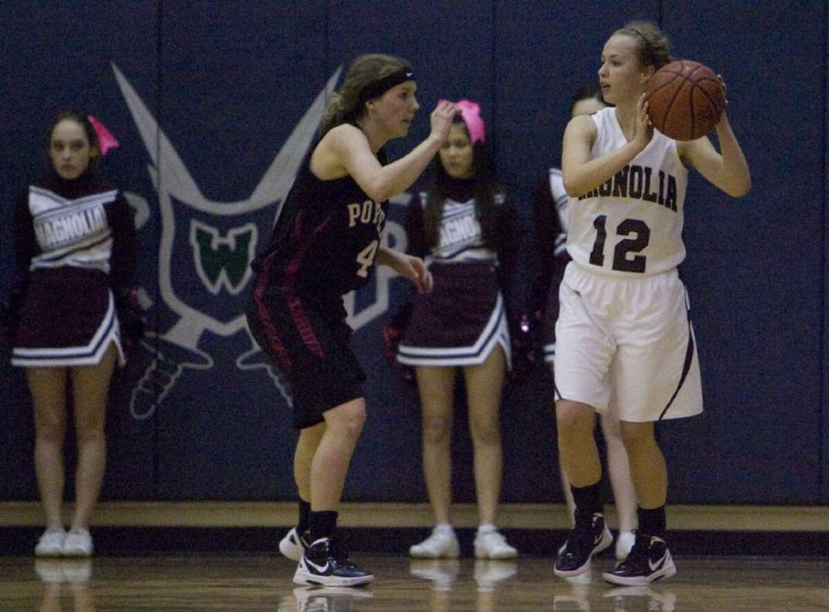 Magnolia's Amy Henry looks for an open teammate as she comes under pressure from Porter's Brandi Barrow during Tuesday's Region III-4A bi-district playoff game at College Park High School.