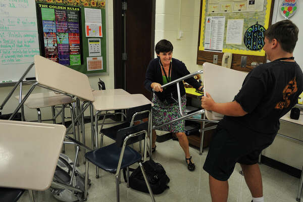 Shelton High School Headmaster Beth Smith, left, playing the role of an armed intruder in the school, is confronted by a student holding a desk during an ALICE drill at the school on Thursday. ALICE is an acronym for Alert, Lockdown, Inform, Counter, and Evacuate.