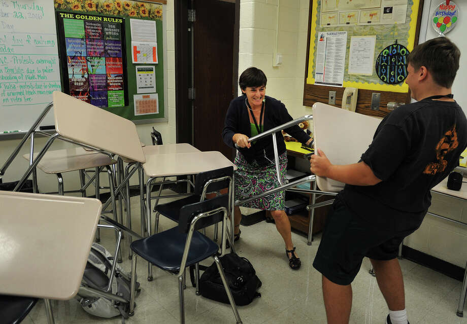 Shelton High School Headmaster Beth Smith, left, playing the role of an armed intruder in the school, is confronted by a student holding a desk during an ALICE drill at the school on Thursday. ALICE is an acronym for Alert, Lockdown, Inform, Counter, and Evacuate. Photo: Brian A. Pounds / Hearst Connecticut Media / Connecticut Post
