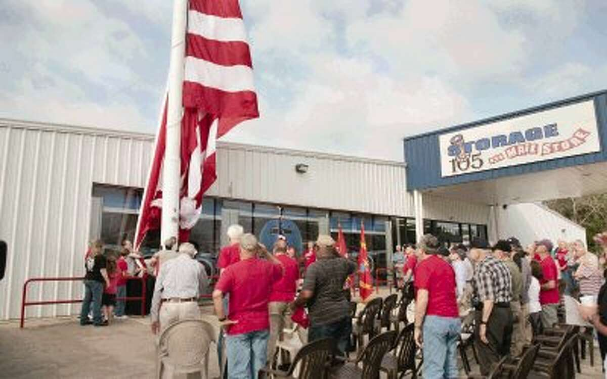 Local veterans salute as the family of Henry Breed Haskell help raise the new 30-foot by 60-foot flag in his honor at Lone Star Honor Flight headquarters on Wednesday.