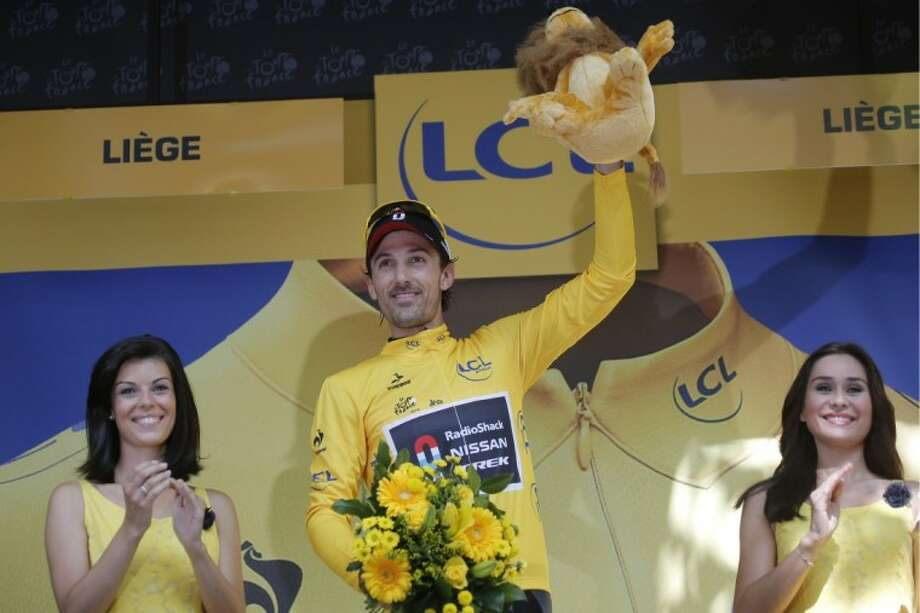 Fabian Cancellara of Switzerland, wearing the overall leader's yellow jersey, celebrates on the podium after winning the prologue of the Tour de France in Liege, Belgium, on Saturday. Photo: Christophe Ena