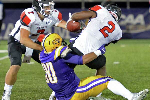 UAlbany's #80 Lukas Repetti tackles Saint Francis's #2 Marcus Bagley just as he takes the hand off from QB Zack Drayer, left, during Saturday's game at Casey Stadium Sept. 24, 2016 in Albany, NY.    (John Carl D'Annibale / Times Union)