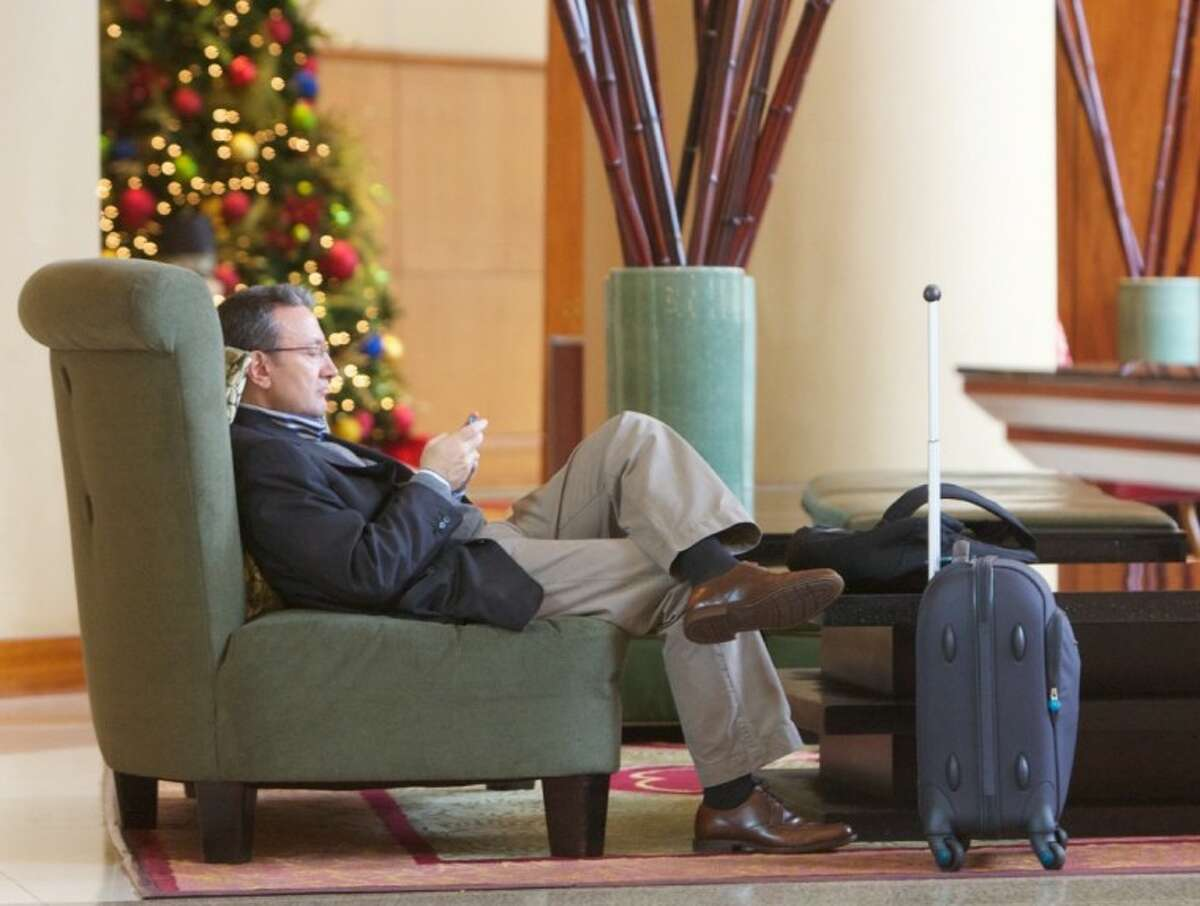 A traveller sits in the lobby of The Woodlands Waterway Marriott Hotel.