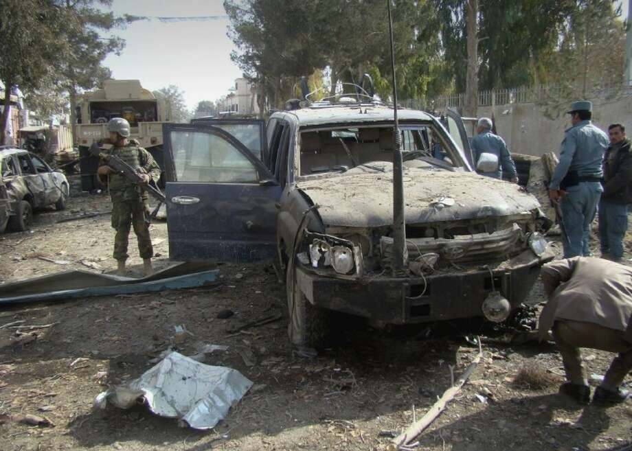 In this Jan. 26, 2012 file photo, an Afghan solider, left, stands guard at the scene of a suicide attack in Lashkar Gah, Helmand province south of Kabul, Afghanistan. Helmand was the centerpiece of President Barack Obama's surge, when he ordered 33,000 additional U.S troops to Afghanistan to help the military with a counterinsurgency plan. Photo: Abdul Khaleq