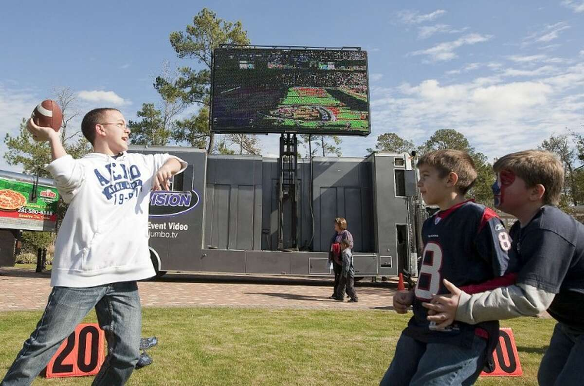 Children play a game of football under large television screens during a Texans tailgate party Sunday at Woodlands Church. See more photos online at www.yourconroenews.com/photos.