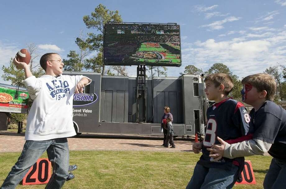 Children play a game of football under large television screens during a Texans tailgate party Sunday at Woodlands Church. See more photos online at www.yourconroenews.com/photos. Photo: Karl Anderson