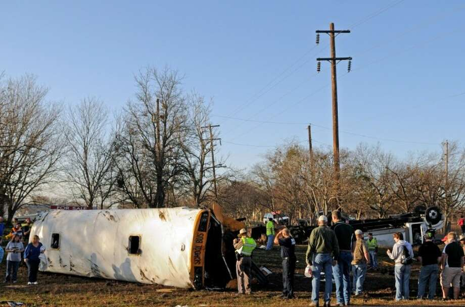 Emergency personnel investigate the scene of a wreck where a tractor-trailer clipped a school bus full of students, flipping the bus onto its side and sending 32 people — 29 of them children — to a central Texas hospital Tuesday in Temple. Police said a 9-year-old boy was ejected through the escape hatch in the bus roof, and the bus driver was knocked unconscious. Photo: Josh Bachman