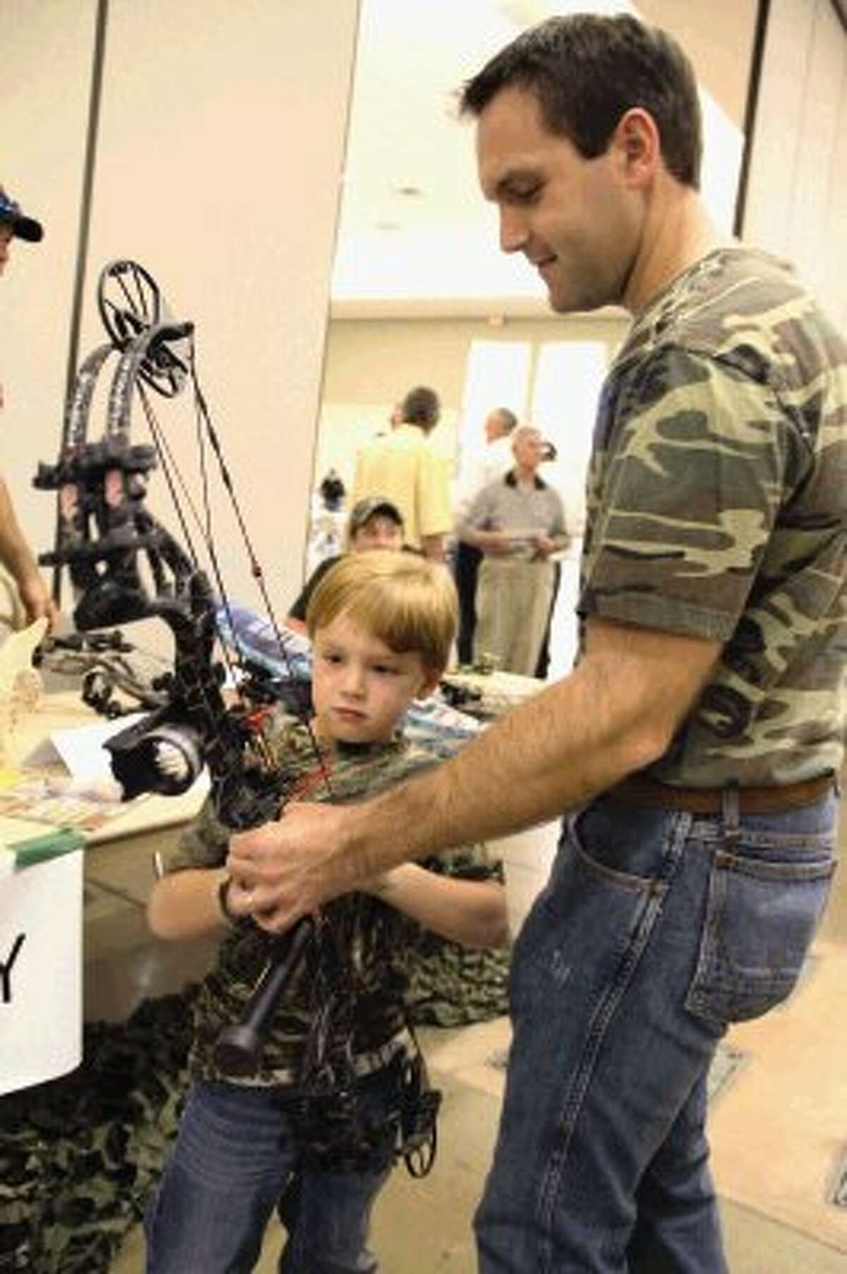 Conroe resident Cam Heathcott shows his son, Harper, a C&S Archery bow at the Outdoor and Sports Banquet on Thursday at the Lone Star Convention and Expo Center.