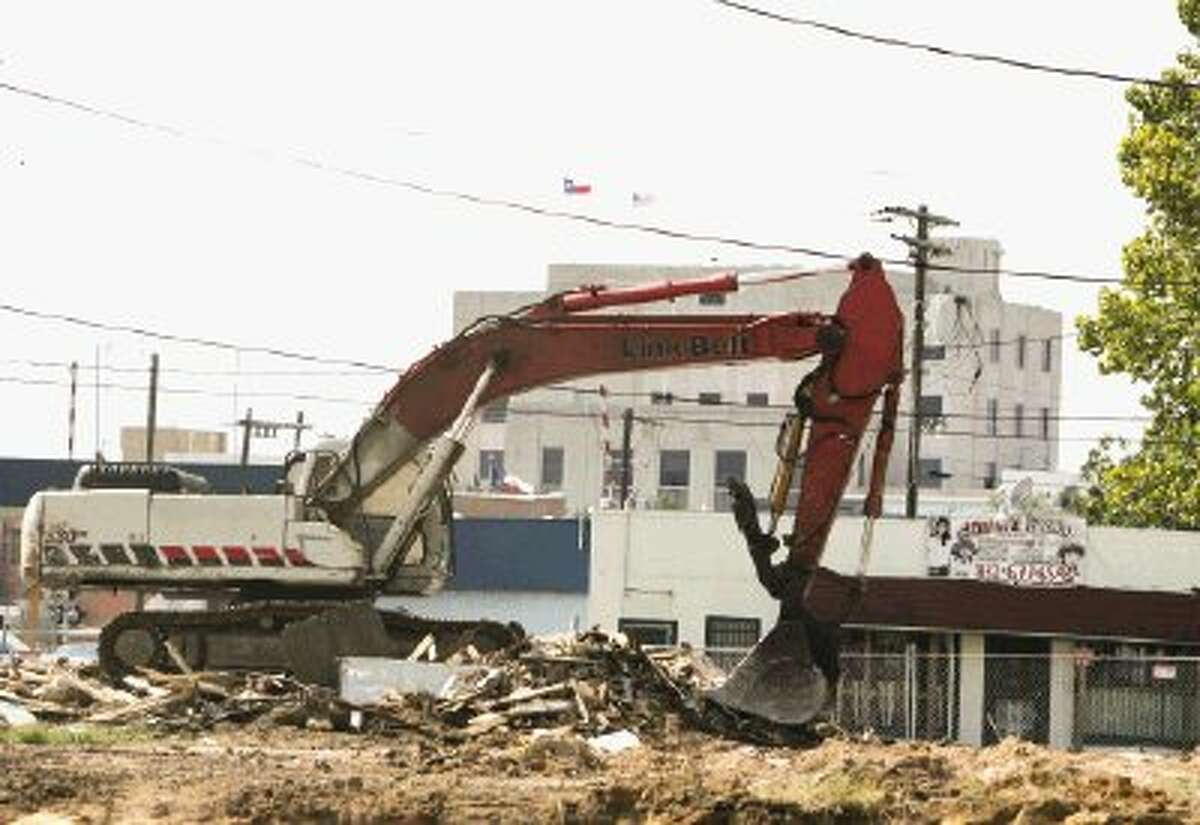 An excavator clears land for a new Fiesta Mart between North First Street and North Second Street on Conroe's east side.