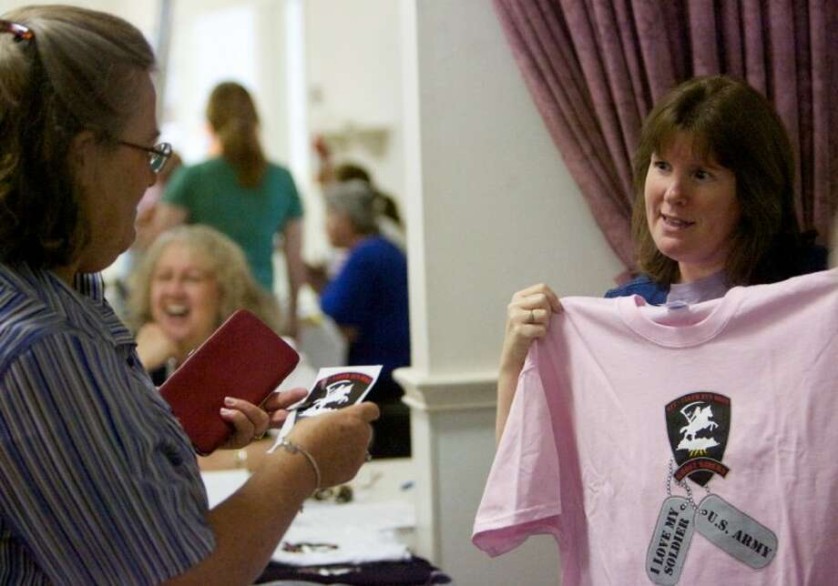 "VFW Ladies Auxiliary Post 4709 member Lisa McCloy displays a shirt for sale bearing the ""Ghost Rider"" logo to a family member of a solider with the 1-158th Aviation Regiment during the regiment's family day celebration Saturday at the KOA campgrounds in Montgomery. Photo: Staff Photo By Eric Swist"