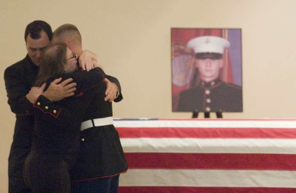 Marine Lance Cpl. Stephan Cassman embraces the parents of Marine Cpl. Joseph Logan during funeral services Wednesday