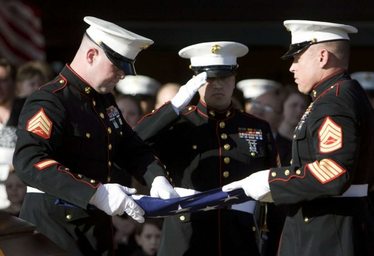 Marine honor guard members fold the flag that draped the casket of Marine Cpl. Joseph Logan during his funeral Wednesday.