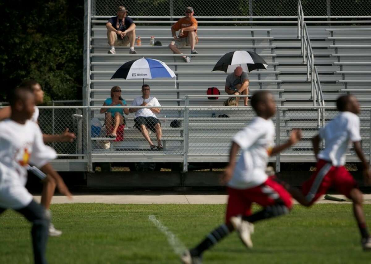 Parents look on as young athletes participate in Saturday's Earl Campbell Football Combine at Conroe High School.