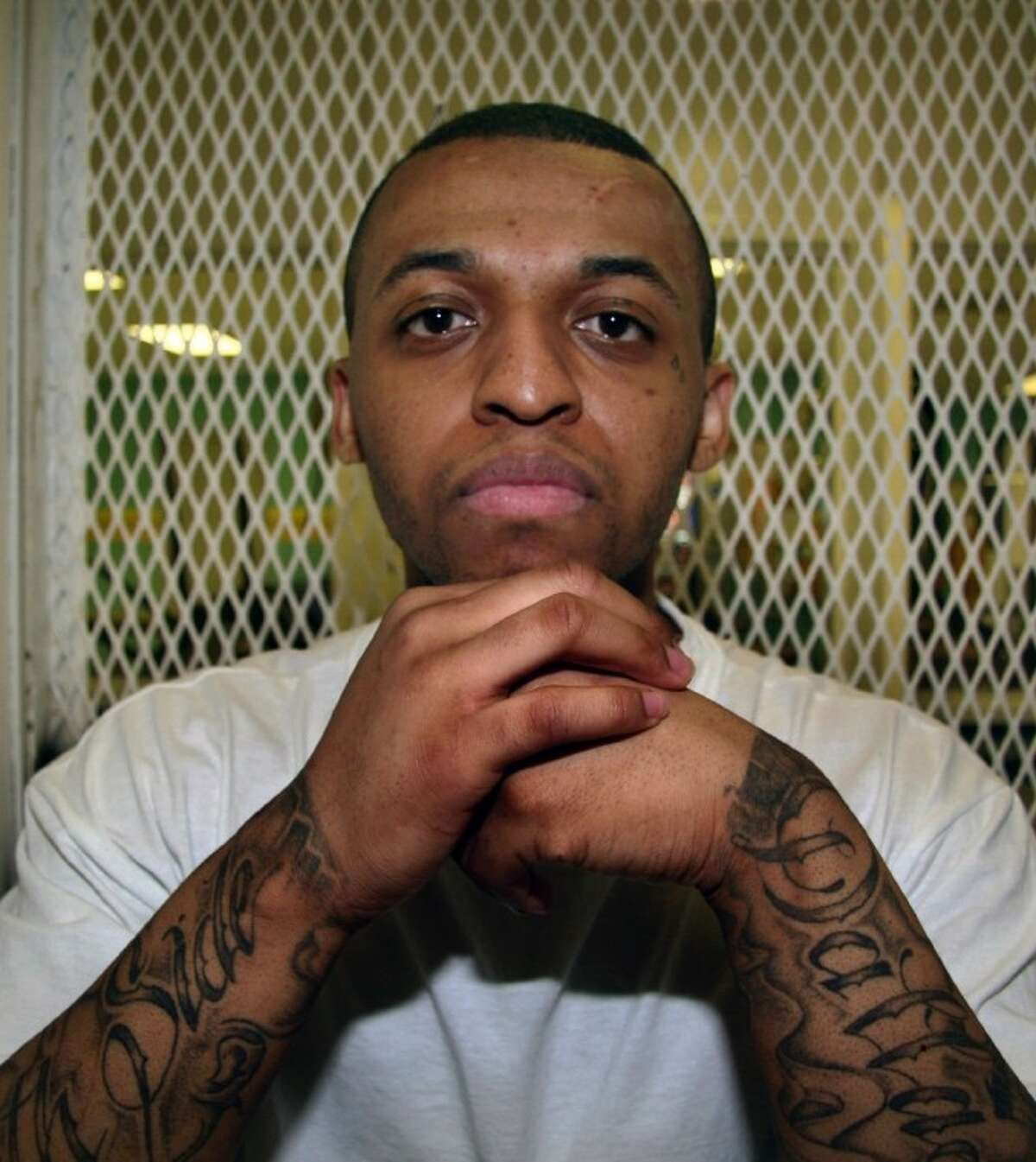 In this Dec. 5, 2012, photo, Texas death row inmate Steven Lawayne Nelson poses for a photo in a visiting cage at the Texas Department of Criminal Justice Polunsky Unit outside Livingston, Texas. Nelson, 25, was convicted of capital murder in mid-October and sent to death row for the 2011 slaying of an Arlington pastor during a robbery.