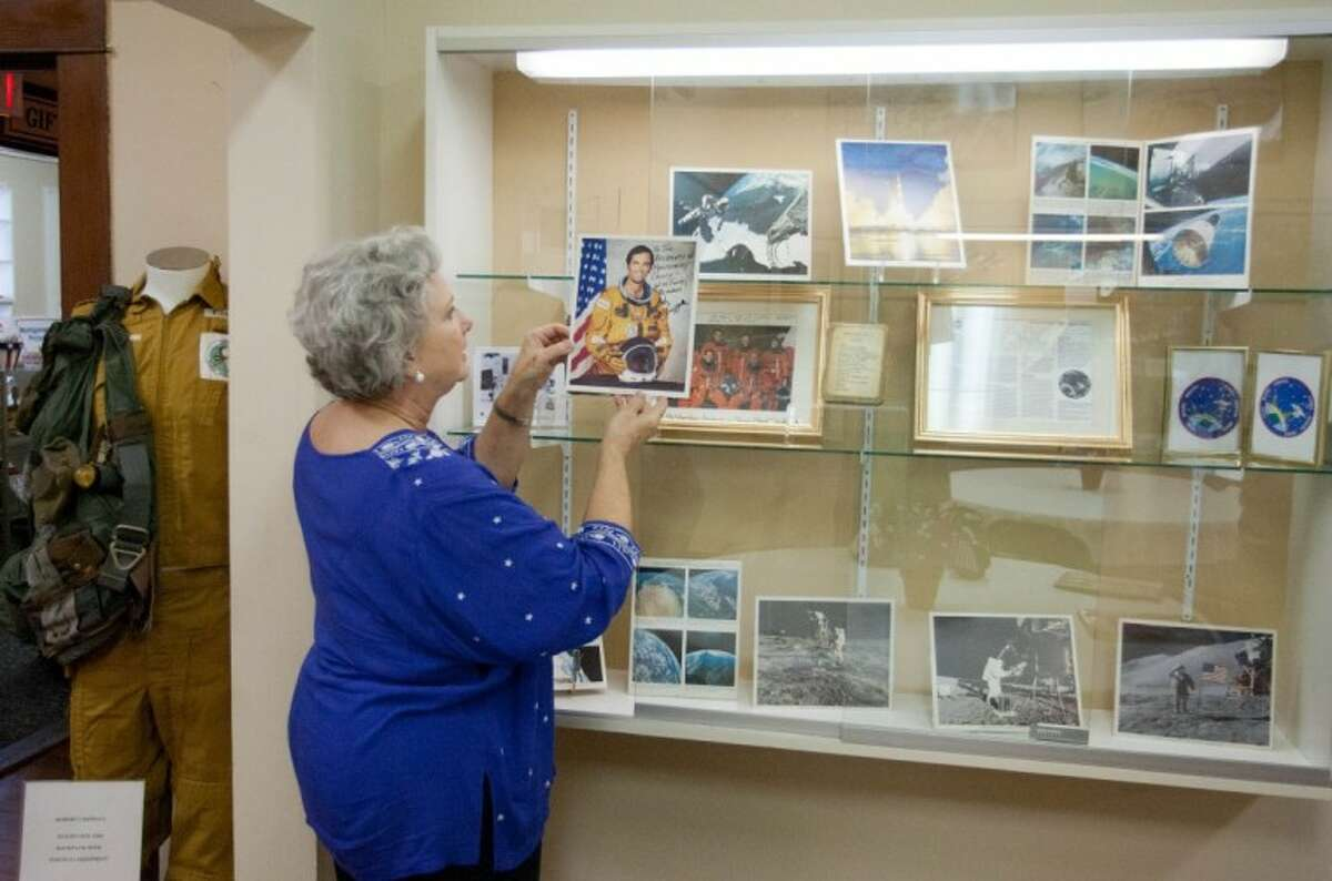 Museum director Sally Copley, of the Heritage Museum of Montgomery County, displays a photo of astronaut Robert L. Crippen, of New Caney, part of the museum's new aeronautical display.