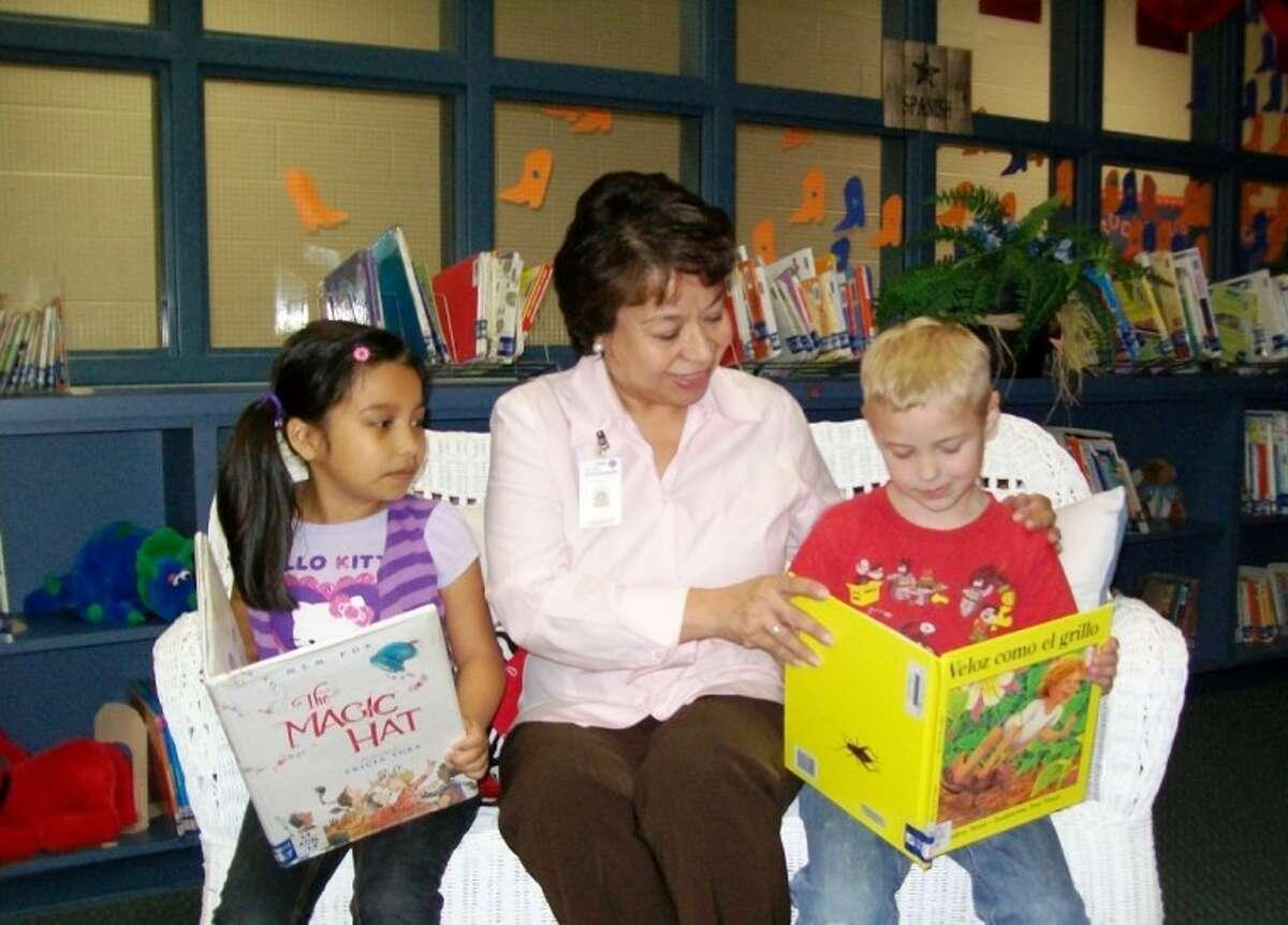 Willis ISD Student Program Coordinator Carmelita Gage reads with students in Cannan Elementary School's Dual Language Program.