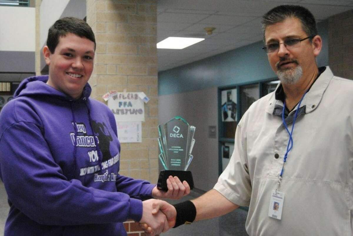 WHS Senior Bryan Moore, left, was selected to represent the state of Texas in the annual DECA International Competition in Salt Lake City Utah April 28 to May 2. Moore won the Accounting Applications section at the 2012 DECA Marketing/Business Competition in Corpus Christi March 3. WHS DECA Adviser Craig Rex, right, congratulates Moore as the first International qualifier to represent Willis High School since 2005.