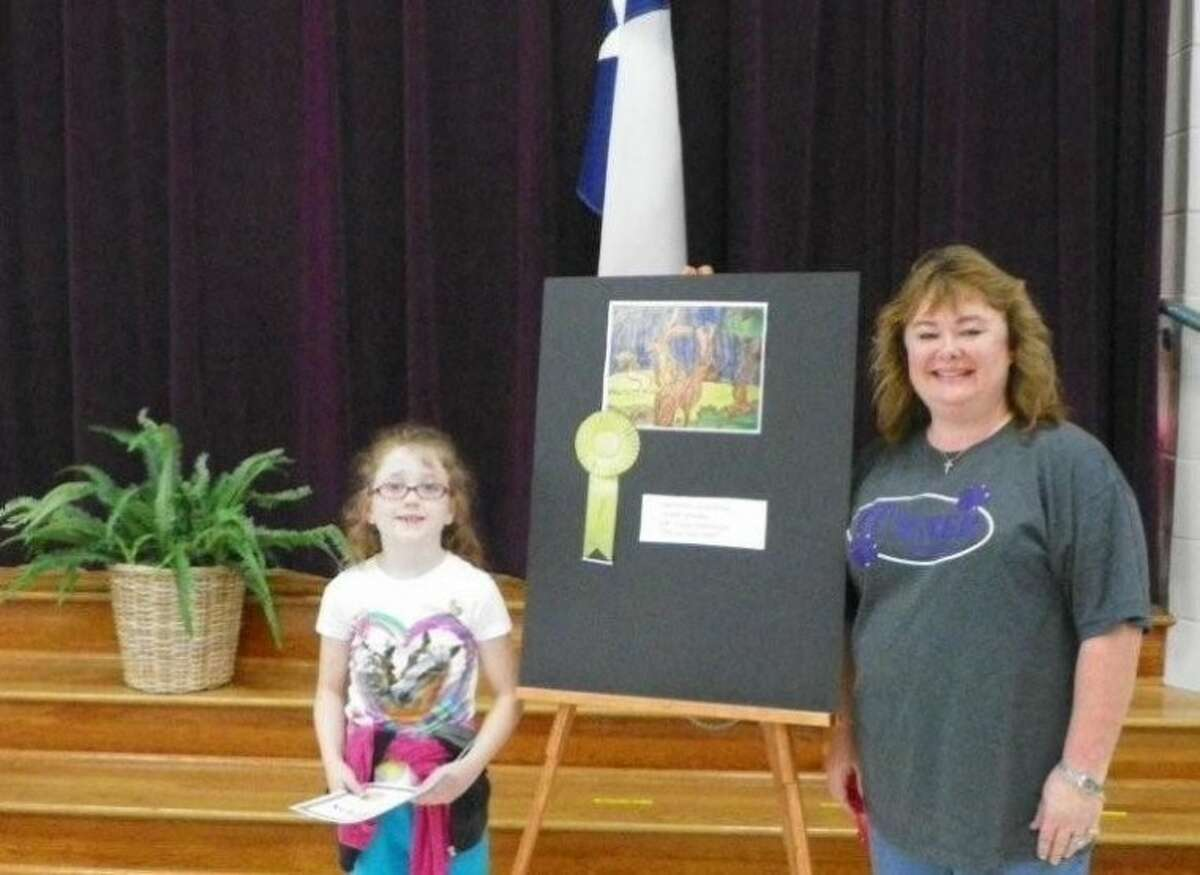 Turner Elementary student Loralee Downey displays the gold medal she won at the Rodeo Art Show to teacher Shannon Martin.