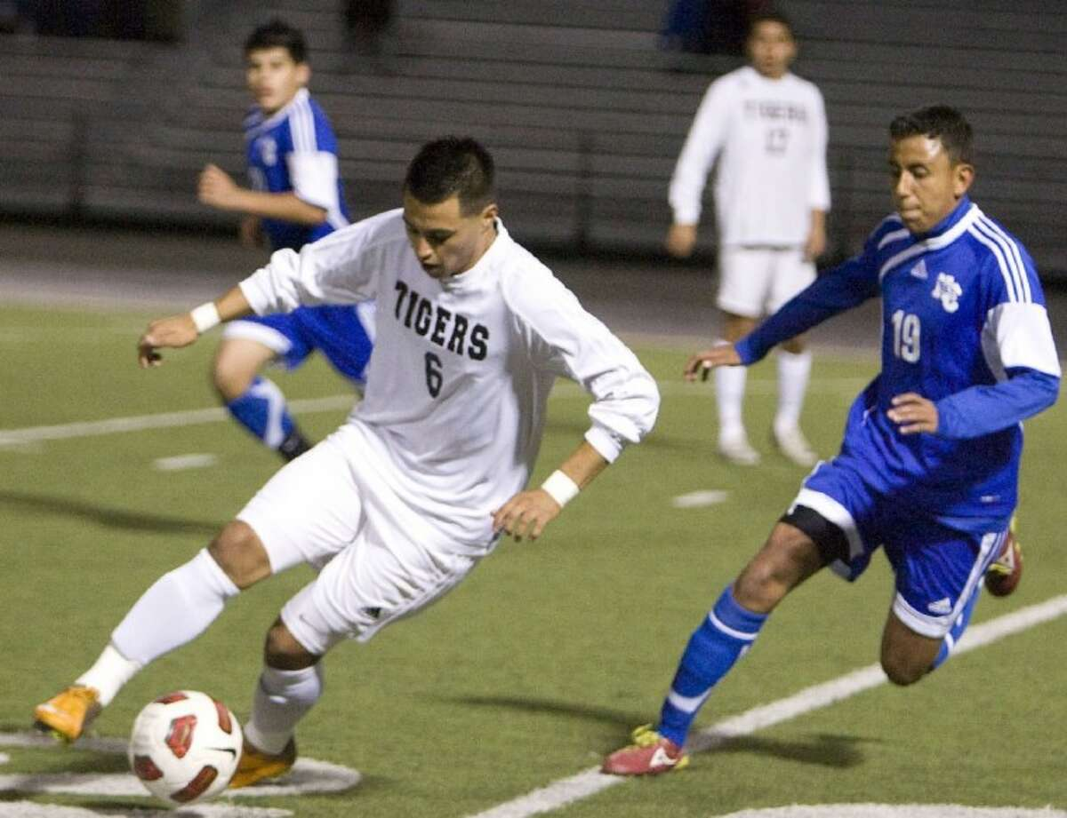 Conroe's Carlos Santos dribbles past New Caney's Daniel Garcia during Tuesday night's game at Moorhead Stadium in Conroe.