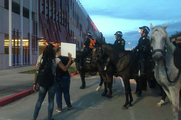 Protesters square off against mounted police in a parking lot during a Black Liver Matter event Saturday night.