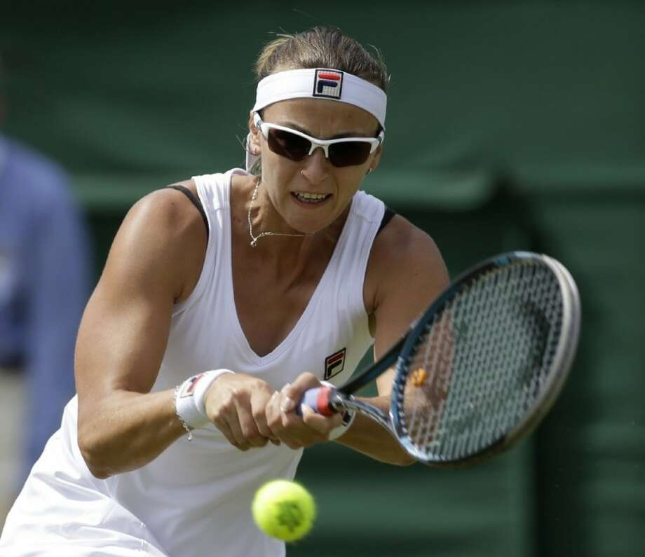 Yaroslava Shvedova of Kazakhstan returns a shot to Sara Errani of Italy during a third round women's singles match at the All England Lawn Tennis Championships at Wimbledon, England, on Saturday. Photo: Sang Tan