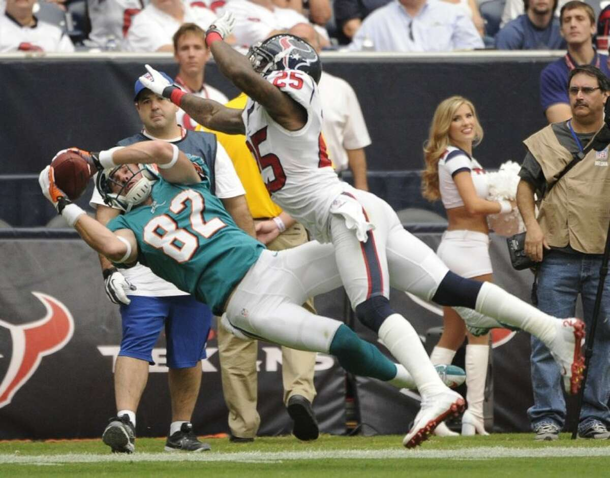 The Miami Dolphins' Brian Hartline (82) leaps for a catch as Houston Texans' Kareem Jackson defends. The Texans rolled to a 30-10 victory.