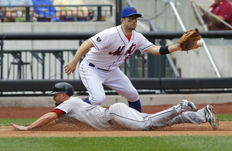 The Houston Astros' Scott Moore slides into third base safely as the Mets' David Wright takes a late throw. The Astros lost 3-1. Photo: Paul Bereswill