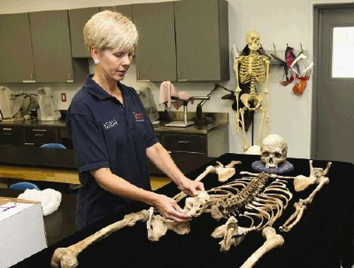 Dr. Joan Bytheway, director of the Southeast Texas Applied Foresic Science Facility at Sam Houston State University, examines the skeletal remains of a donor body.
