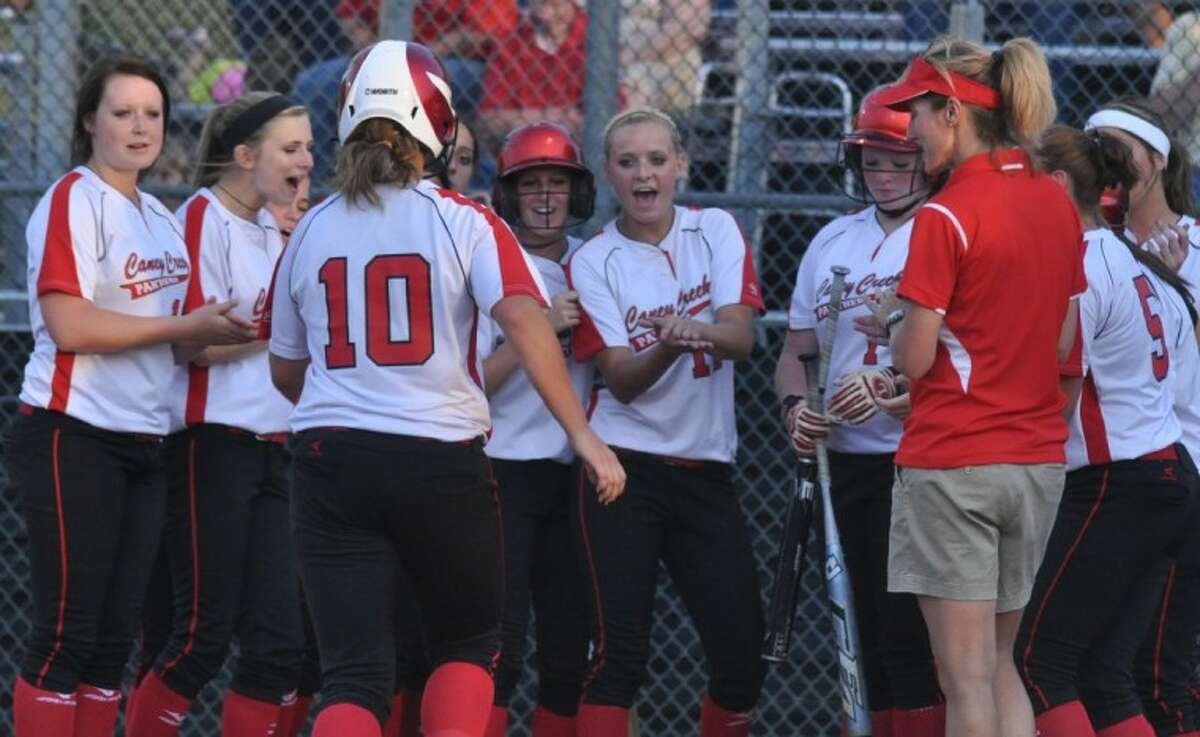 Caney Creek players welcome Lorraine Negrini to the plate after hitting a solo homer against Montgomery in a Region III-4A bi-district playoff game at Conroe High School on Friday.