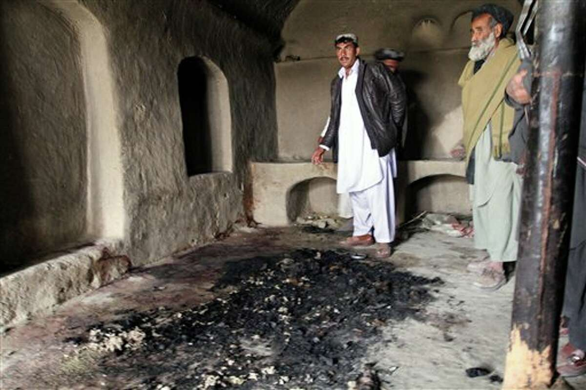 In this Sunday, March 11, 2012 photo, men stand next to blood stains and charred remains inside a home where witnesses say Afghans were killed by a U.S. soldier in Panjwai, Kandahar province south of Kabul, Afghanistan. (AP Photo/Allauddin Khan)