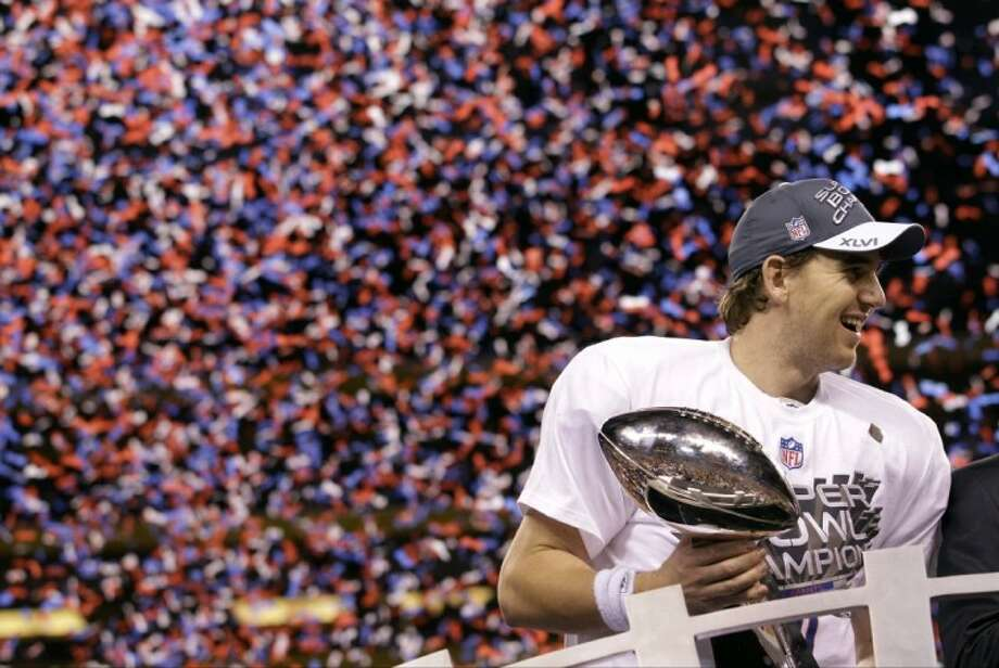 New York Giants quarterback Eli Manning holds up the Vince Lombardi Trophy while celebrating his team's 21-17 win over the New England Patriots in the NFL Super Bowl XLVI Sunday in Indianapolis. Photo: David J. Phillip