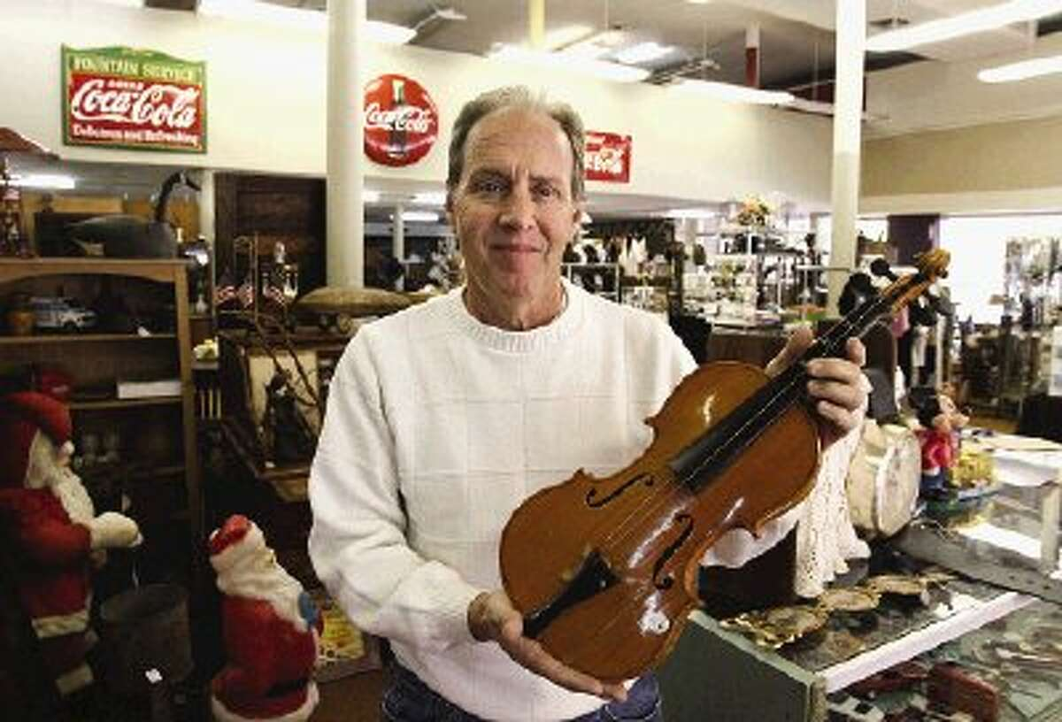 Conroe Central Market owner Michael Canada shows off an old violin, one of the nostalgic items available at his new antique and collectible mall in downtown Conroe.